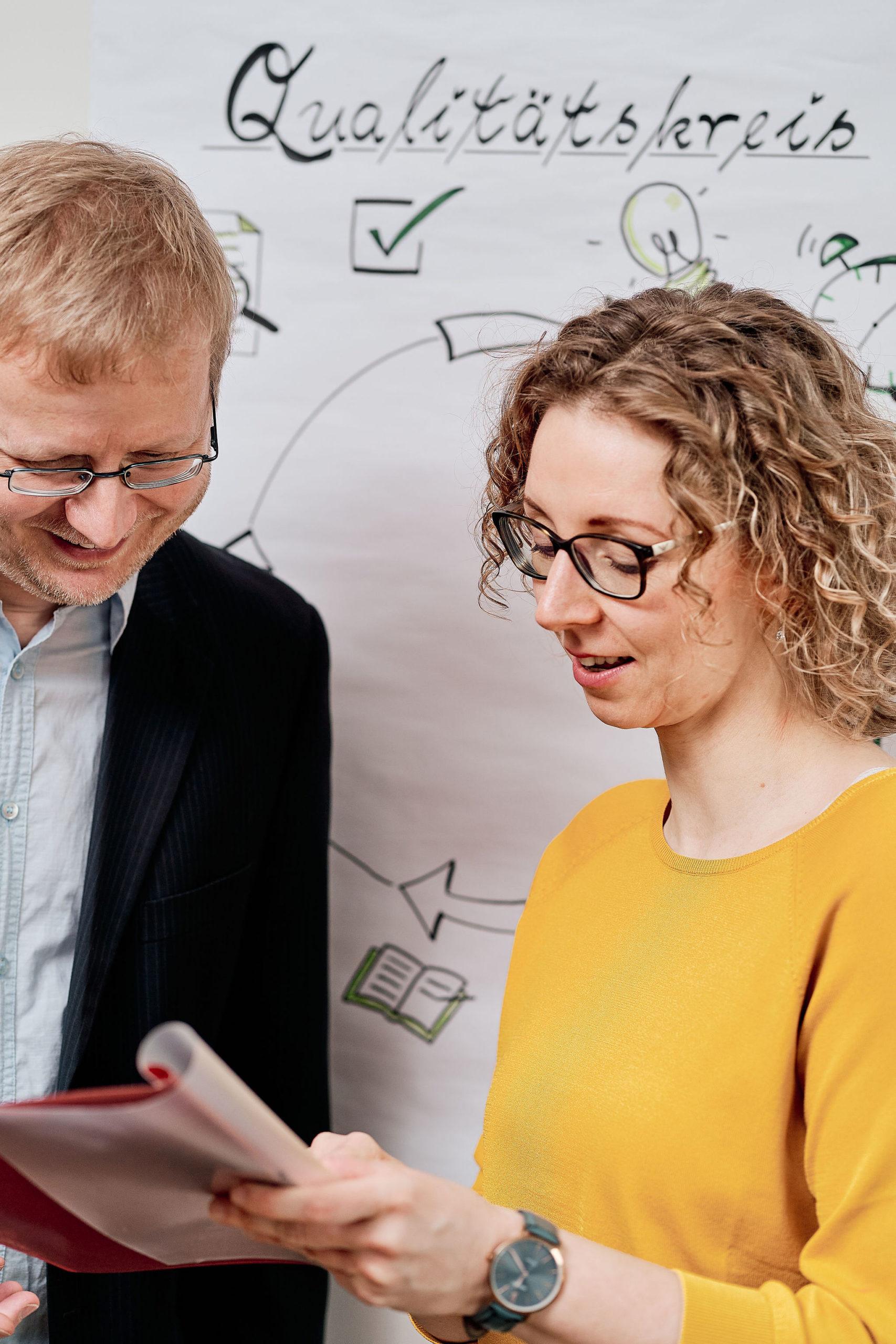Eine Frau und ein Mann unterhalten sich vor einem gezeichneten Qualitätskreislauf
