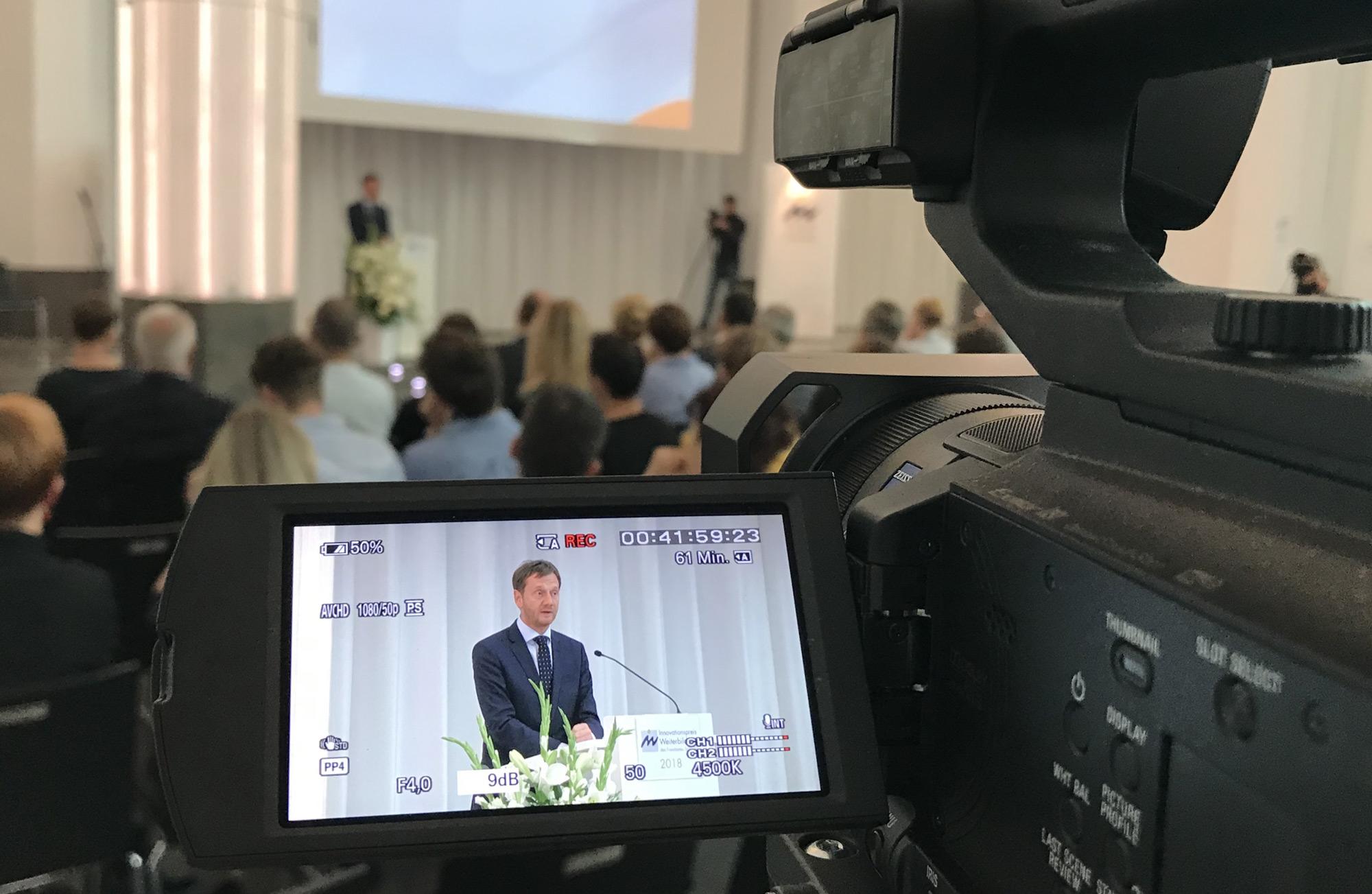 Blick durch ein Kameradisplay bei einer Veranstaltung. Auf der Bühne spricht Ministerpräsident Kretschmer