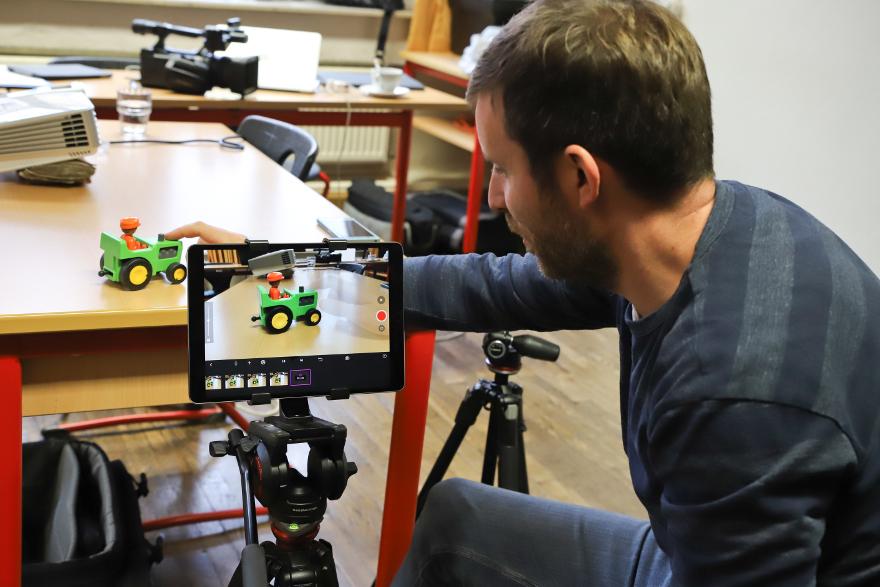 Ein Mann erstellt einen Stop-Motion-Film mit einem Tablet.